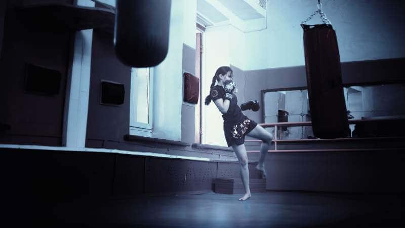 woman-training-in-a-gym-kicking-a-training-bag