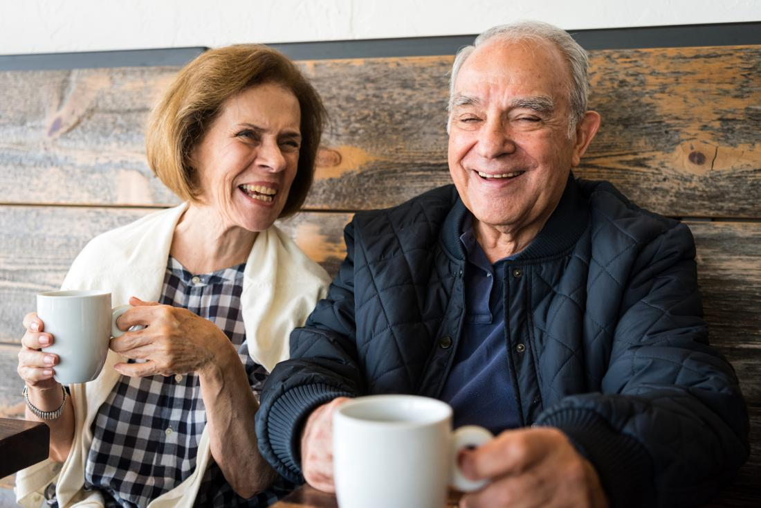 Older adults laughing with coffee