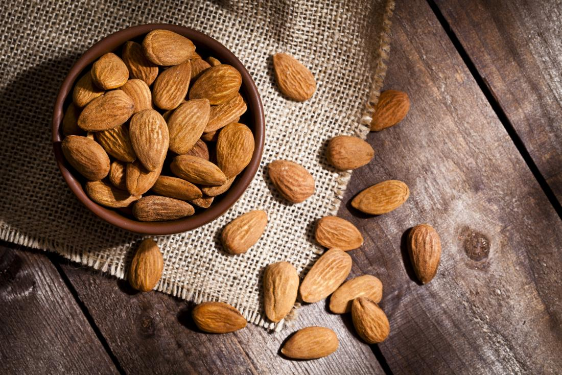 Bowl of almonds spilling out on wooden.