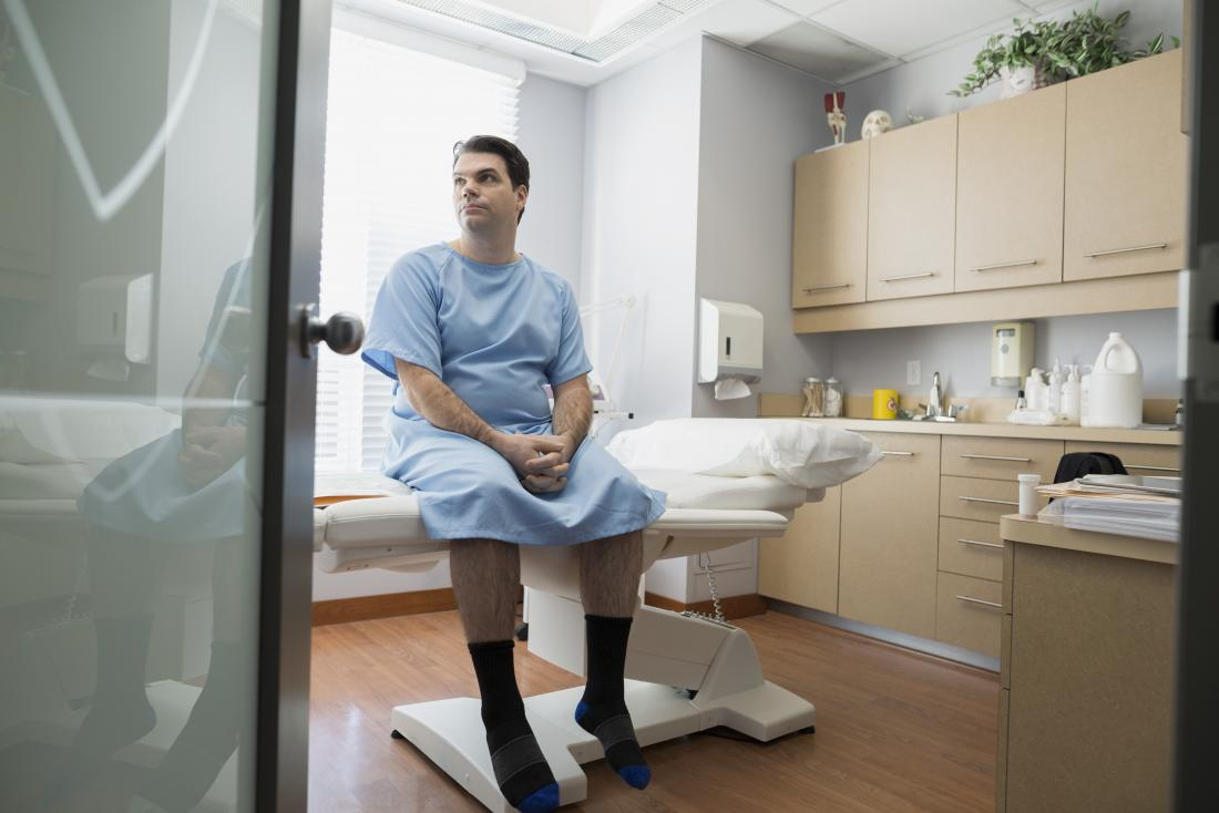 Man in hospital gown sitting on bed in doctor's office waiting to be tested for chlamydia in men