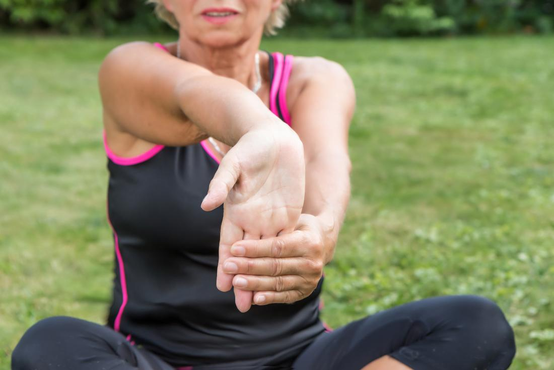 Woman performing wrist flexion stretches