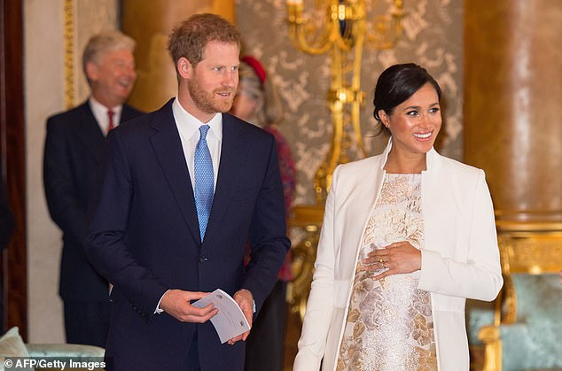 The world is still waiting for news of the birth of Prince Harry and Meghan's first child. They are pictured together at Buckingham Palace on March 5