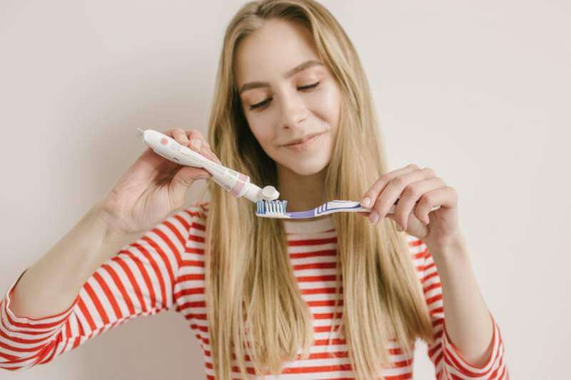 cute-young-girl-with-tooth-brush-is-pressing-a-toothpaste-on-it