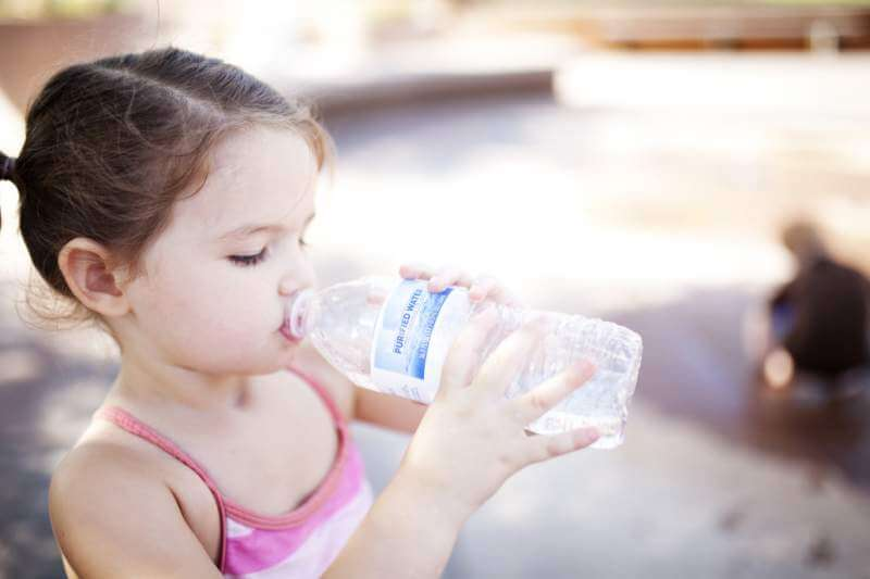 little-girl-drinks-from-a-water-bottle-while-swimming