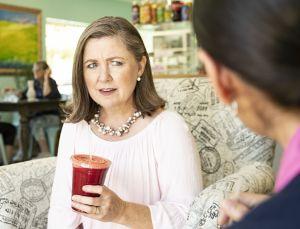 A woman struggles to hear a friend speak.