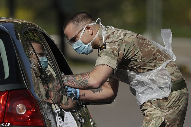 A NHS or care worker being tested by a soldier for COVID-19 at a drive-through testing centre in a car park at Chessington World of Adventures yesterday
