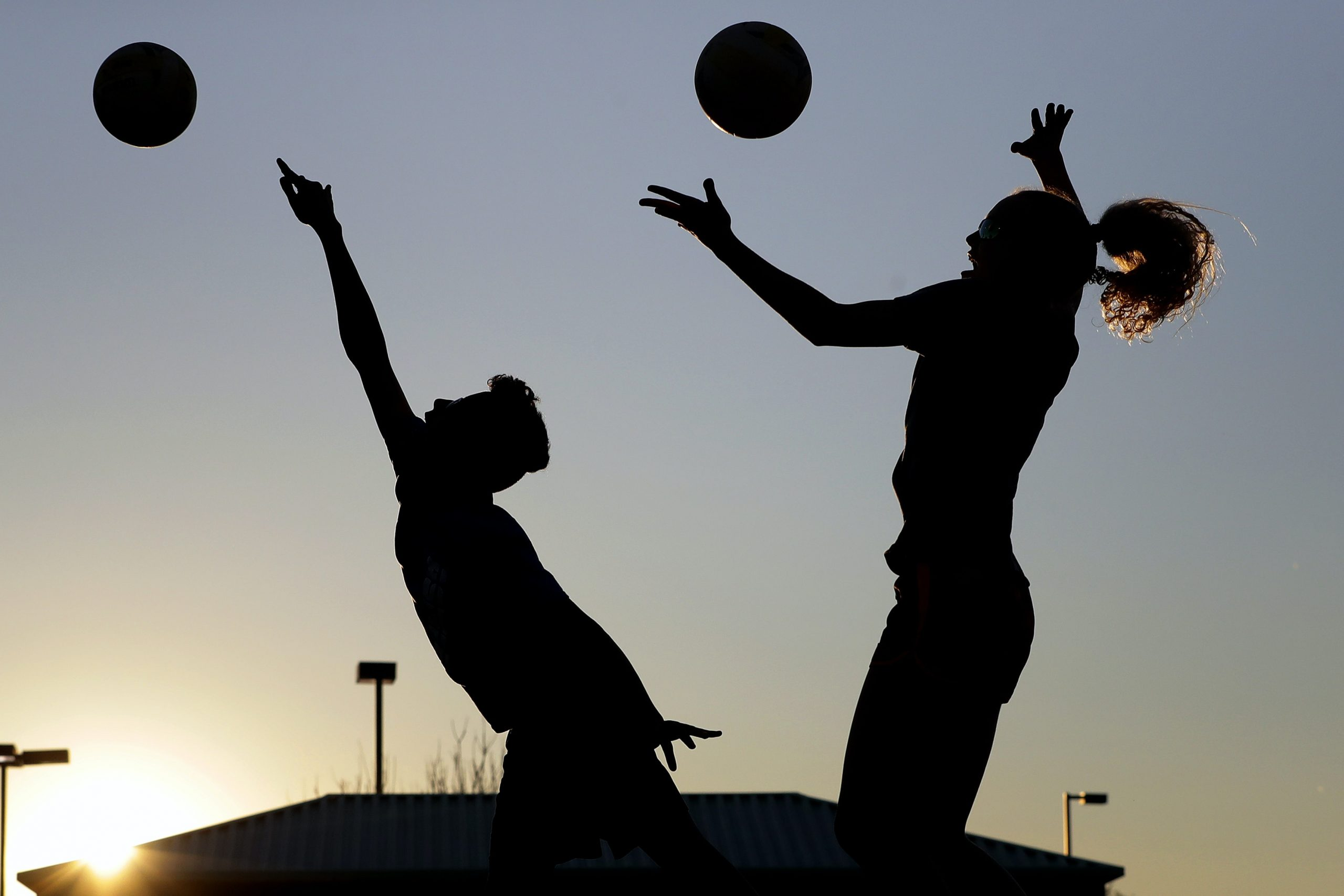 Two teenagers practicing volleyball.