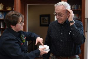 A fire safety technician tests a fire alarm with an older man who has hearing loss.